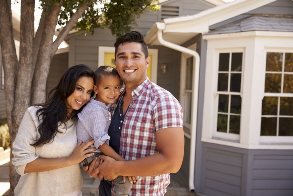 Couple with baby in front of their house
